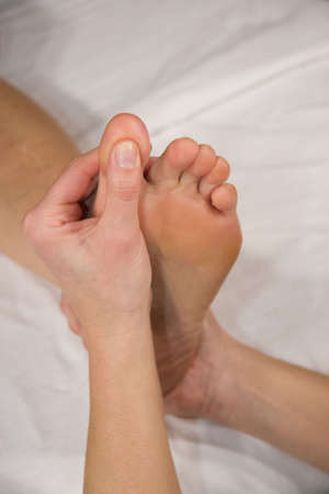 orthopaedist: a closeup of a foot of a natural mature woman having a foot reflex zone massage at her big toe Stock Photo