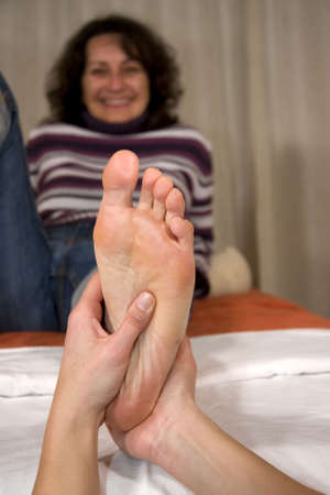 a smiling natural mature woman having a foot reflex zone massage at the sole of her foot photo