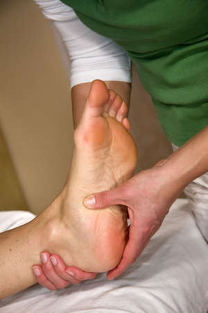 foot doctor: a closeup of a foot of a natural mature woman having a foot reflex zone massage at the sole of her foot