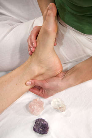a closeup of a foot of a natural mature woman having a foot reflex zone massage at her achilles tendon Stock Photo