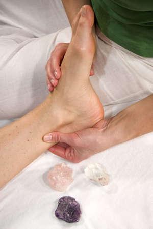 eine Nahaufnahme eines Fußes einer natürlichen Reife Frau, die mit einen Fuß reflex Zone-Massage auf ihre Achillessehne