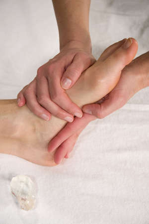 a closeup of a foot of a natural mature woman having a foot massage at the sole of her foot Stock Photo