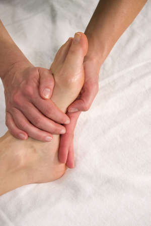 orthopaedist: a closeup of a foot of a natural mature woman having a foot massage at the sole of her foot Stock Photo