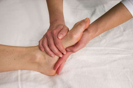 a closeup of a foot of a natural mature woman having a foot massage at the sole of her foot photo