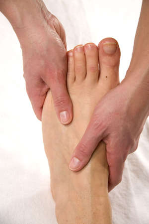 a closeup of a foot of a natural mature woman having a foot massage at the instep of her foot photo