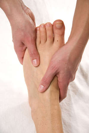 a closeup of a foot of a natural mature woman having a foot massage at the instep of her foot