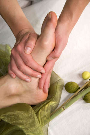 a wellness composition showing a closeup of a foot of a natural mature woman having a massage at the sole of her foot photo