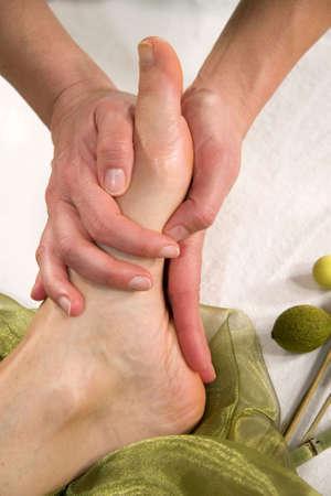 eine Wellness-Komposition zeigt eine Nahaufnahme eines Fußes einer natürlichen Reife Frau, die mit eine Massage auf der Fußsohle Ihr Standard-Bild
