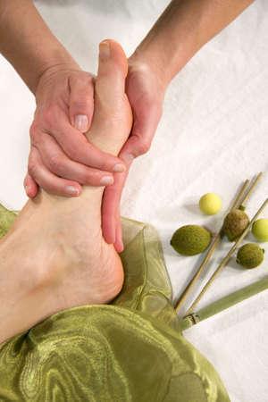 eine Wellness-Komposition zeigt eine Nahaufnahme eines Fußes einer natürlichen Reife Frau, die mit eine Massage auf der Fußsohle Ihr
