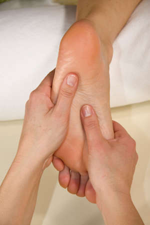 a closeup of a foot of a natural mature woman having a foot reflex zone massage at the sole of her foot photo