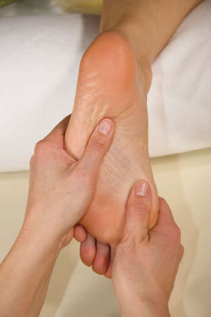 a closeup of a foot of a natural mature woman having a foot reflex zone massage at the sole of her foot