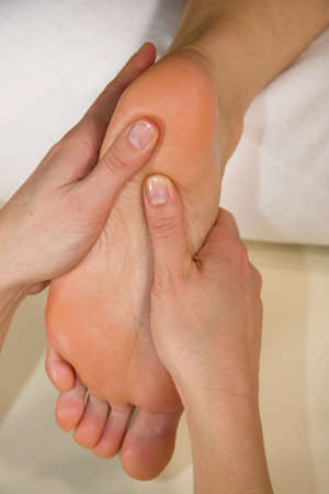 orthopaedist: a closeup of a foot of a natural mature woman having a foot reflex zone massage at the heel of her foot Stock Photo