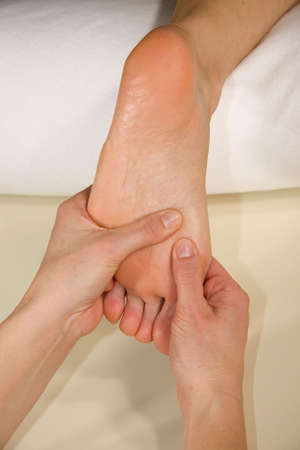 hardening: a closeup of a foot of a natural mature woman having a foot reflex zone massage at the ball of her foot
