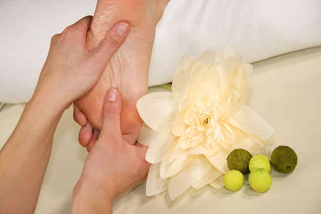 a wellness composition showing a foot of a natural mature woman having a foot reflex zone massage and a flower photo