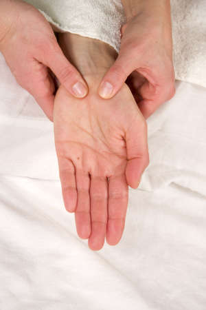 hardening: a closeup of a hand of a natural mature woman having a hand reflex zone massage of her thenar