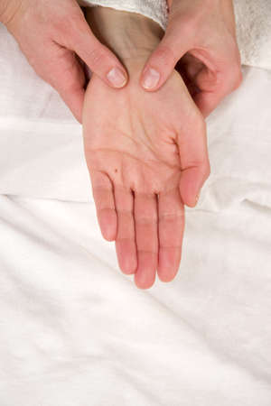 orthopaedist: a closeup of a hand of a natural mature woman having a hand reflex zone massage at her thenar
