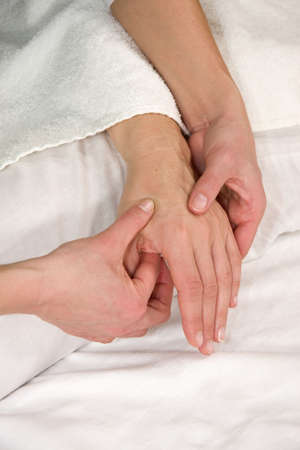 hardening: a closeup of a hand of a natural mature woman having a hand reflex zone massage at her back of the hand Stock Photo