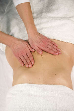 a closeup of a natural mature woman having a massage at her abdomen photo