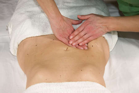 a closeup of a natural mature woman having a massage at her appendix