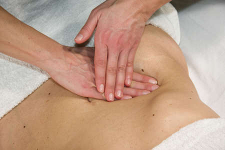 a closeup of a natural mature woman having a massage at her abdomen in the appendix region