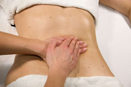 orthopaedist: a closeup of a natural mature woman having a massage at her abdomen