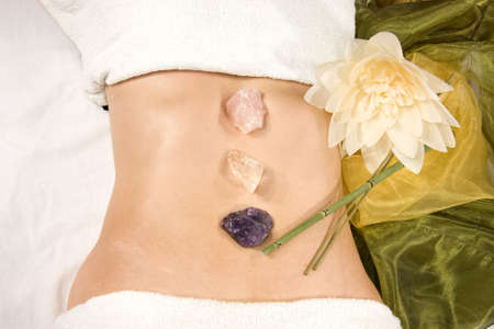 a wellness composition showing the abdomen of a natural mature woman, stones, a flower and a silk scarf photo