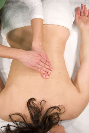 a natural mature woman having a massage at her back muscle