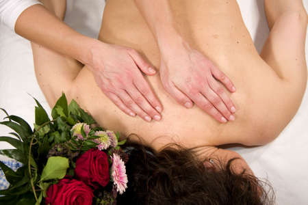 orthopaedist: a wellness composition showing a woman having a massage at her back and a bunch of flowers lying next to her head