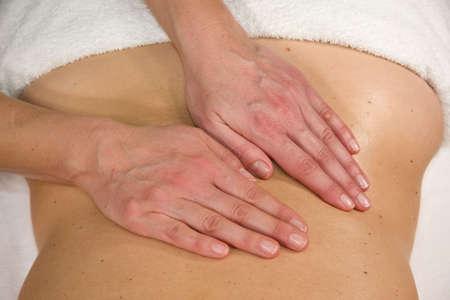 a closeup of a natural mature woman having a massage at her lumbar region Stock Photo - 6596643