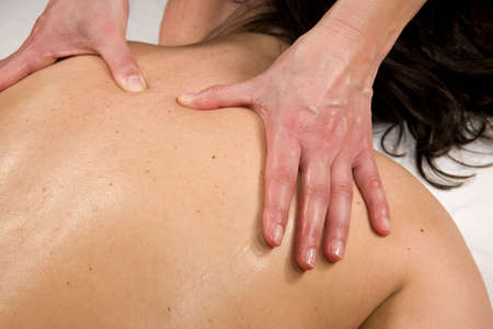 orthopaedist: a natural mature woman having a massage at her back muscle