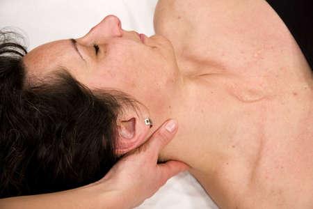 a natural mature woman having a massage at her neck photo