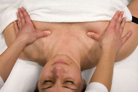 orthopaedist: a natural mature woman having a massage at her chest