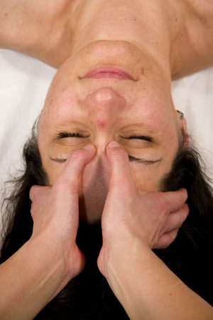 orthopaedist: a natural mature woman having a massage at the root of her nose