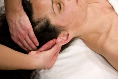 a natural mature woman having a massage at her auricle photo