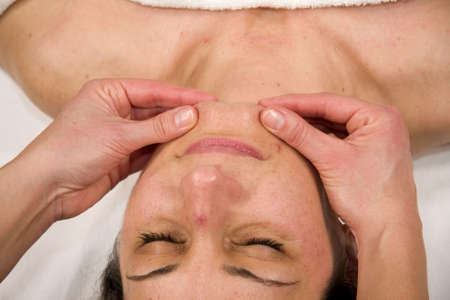 orthopaedist: a natural mature woman having a massage at her chin