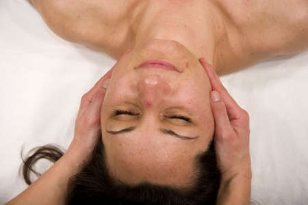 orthopaedist: a natural mature woman having a massage at her masseters and at her jaw