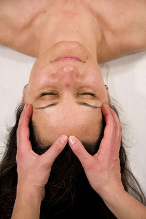 a natural mature woman having a massage at her forehead photo