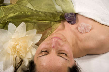 a wellness composition showing a natural mature woman on a massage bed, a flower, stones and a silk scarf Stock Photo - 6596739