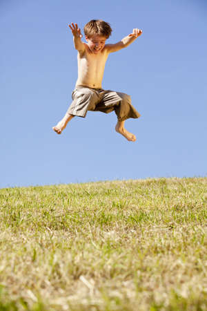 A laughing and happy eight years old jumping boy, photographed in the summer sun with blue sky in the background photo