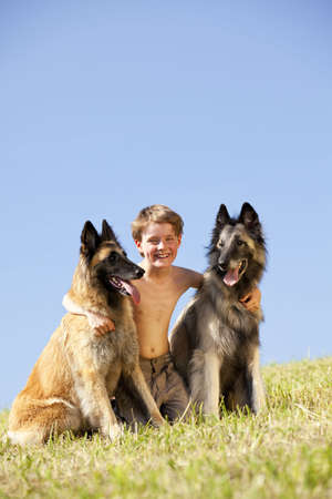 A smiling cute eight years old boy with two Belgian shepherds, photographed in the summer sun with blue sky in the background