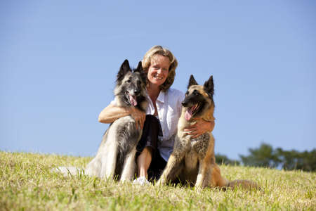 eine glückliche schöne lächelnd Frau umarmt ihre Hunde, belgische Schäferhunde, fotografiert in der Sommersonne mit blauen Himmel im Hintergrund