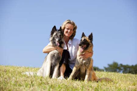 mujer con perro: una feliz hermosa mujer sonriente abrazando a sus perros pastores belgas, fotografiado en el sol de verano con cielo azul en el fondo