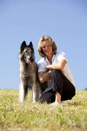 a happy beautiful smiling woman with her dog, a Belgian shepherd, photographed in the summer sun with blue sky in the background photo