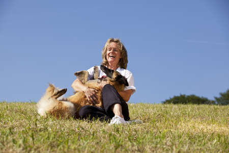 a happy beautiful smiling woman playing with her dog, a Belgian shepherd, photographed in the summer sun with blue sky in the background