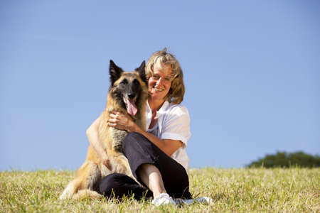a happy beautiful smiling woman hugging her dog, a Belgian shepherd, photographed in the summer sun with blue sky in the background photo