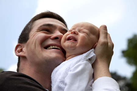 A desperate young father trying to becalm his 7 weeks old crying daughter Stock Photo