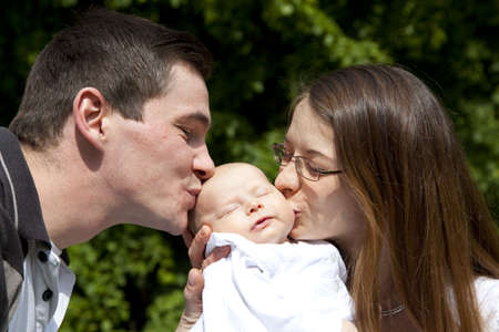 A young father and a young mother kissing their sleeping 7 weeks old daughter photo