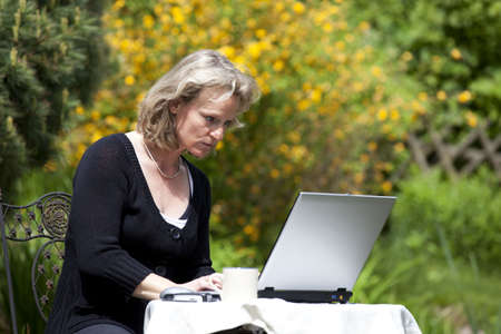 A beautiful mature blond woman sitting in her garden and working concentrated at her laptop Stock Photo - 7290696