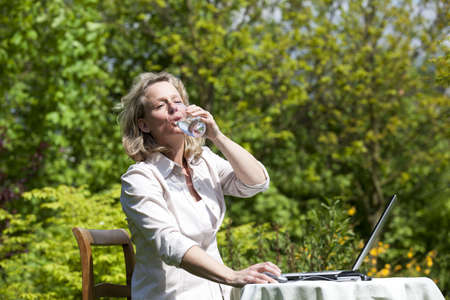 A beautiful mature blond woman sitting in her garden at her laptop and drinking a glass of water