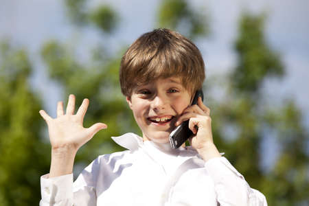 A handsome eight years old boy with a cellphone raising his hand Stock Photo - 7290586